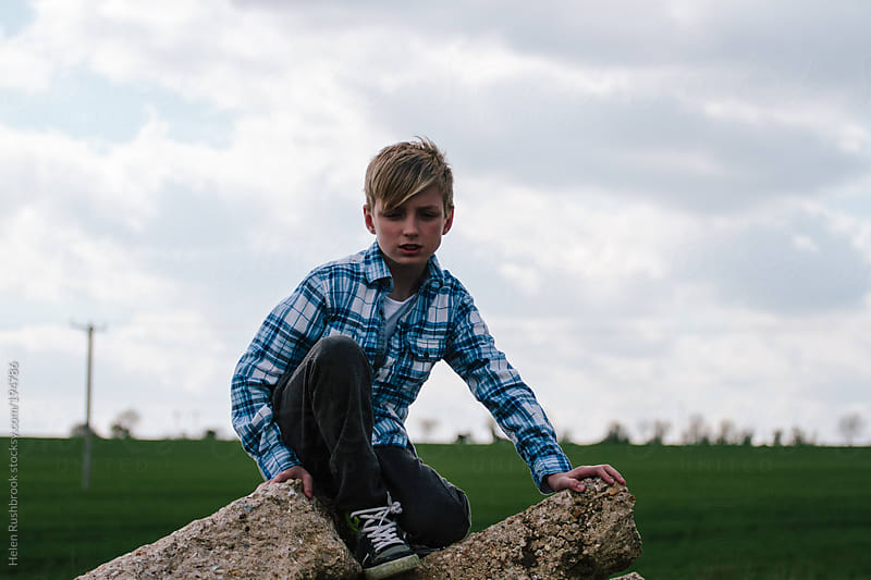 Trendy young boy sitting on a pile of rubble on waste ground. by Helen Rushbrook for Stocksy United