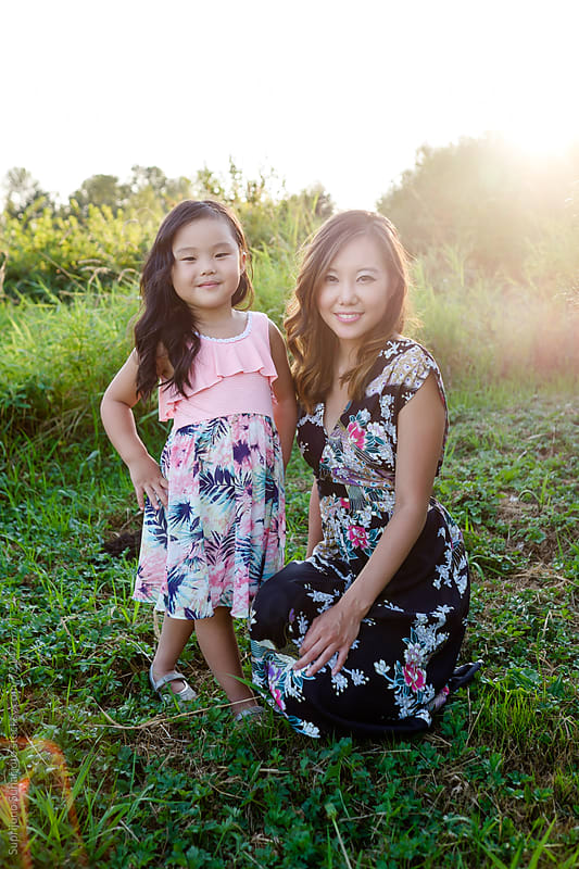 Happy Asian mother and daughter in a park by Suprijono Suharjoto for Stocksy United