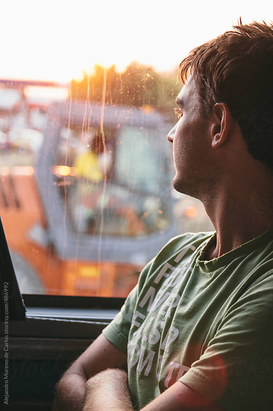 Young man looking out of the window traveling in a bus at sunset by Alejandro Moreno de Carlos for Stocksy United