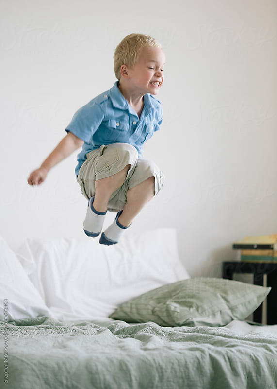 Boy Jumping on Bed by Stephen Morris for Stocksy United
