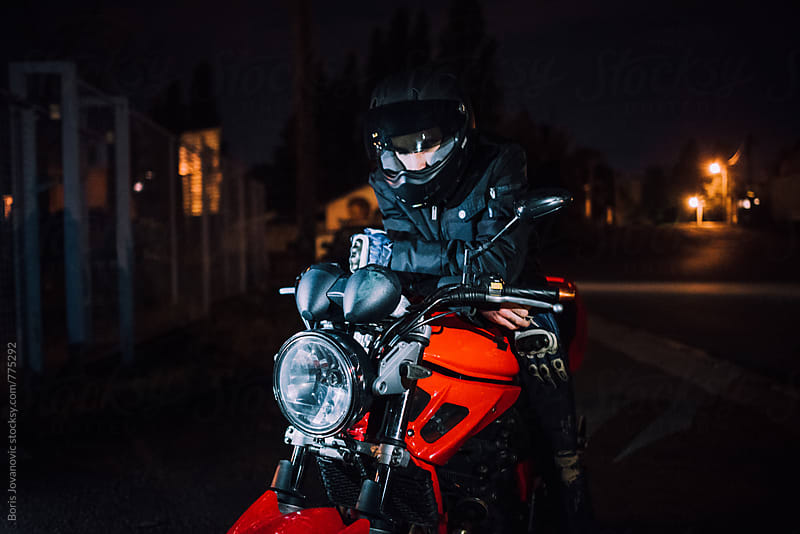 Portrait of biker sitting on his bike with helmet by Boris Jovanovic for Stocksy United