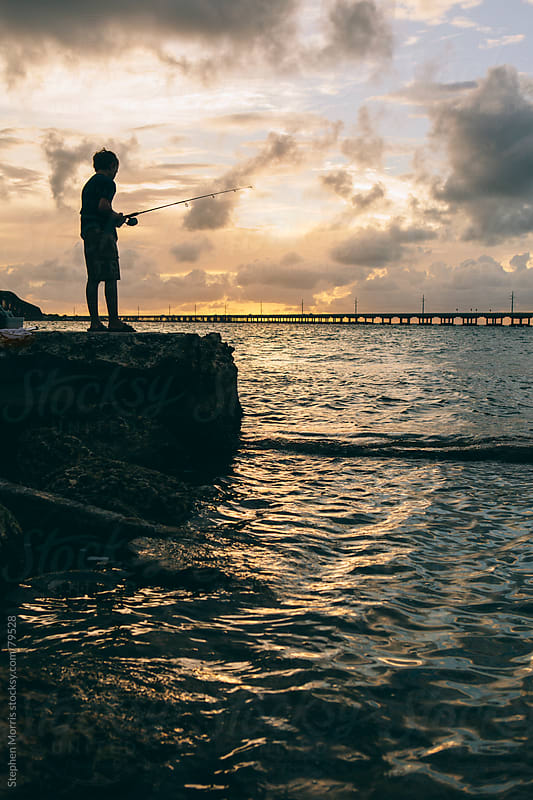 Boy Fishing at Sunset by Stephen Morris for Stocksy United