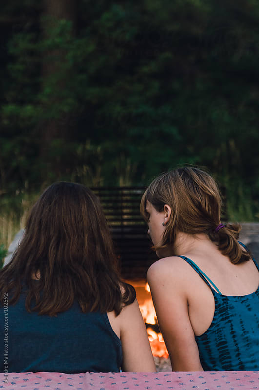 two girls (sisters) making music by camping fire by Deirdre Malfatto for Stocksy United