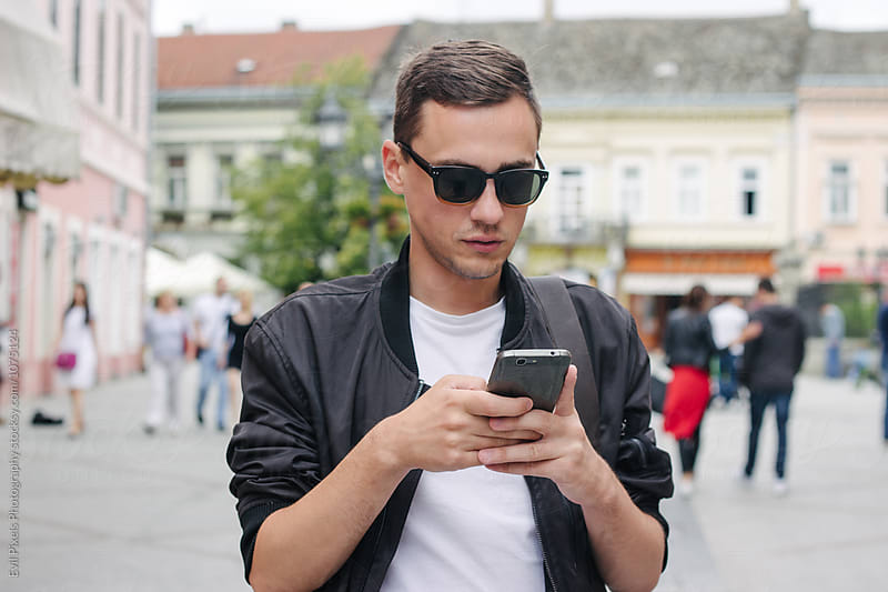 Portrait of a young male model with his phone on the street by Branislava Živić for Stocksy United