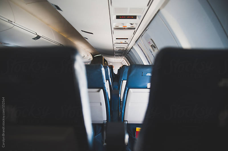 empty seats on an airplane by Carolyn Brandt for Stocksy United
