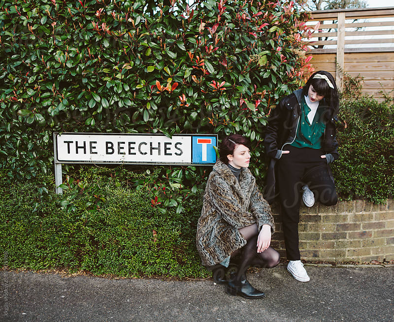 Two young women in the street next to a sign by kkgas for Stocksy United