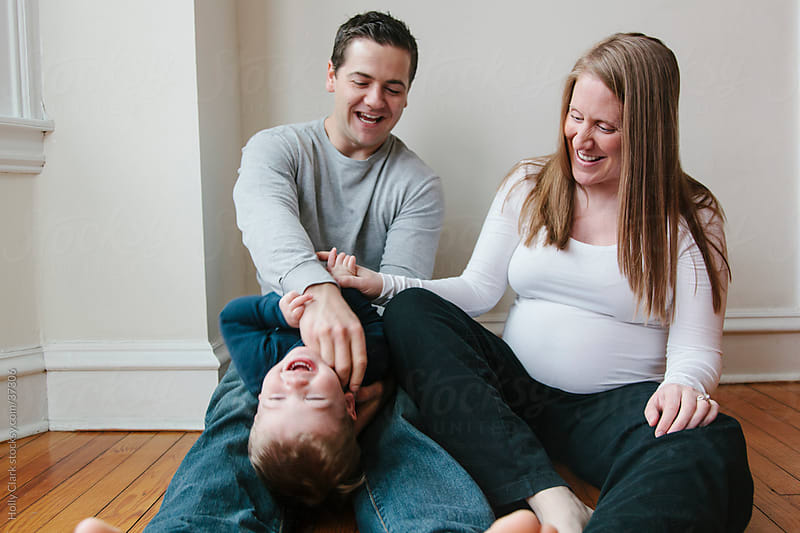 A Pregnant Mother and Father tickle their Son by Holly Clark for Stocksy United