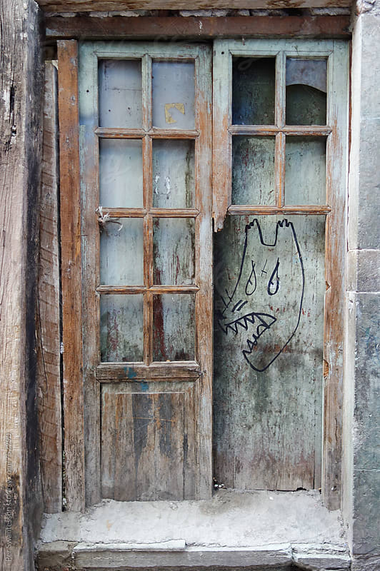 Street art monster behind old door by Per Swantesson for Stocksy United