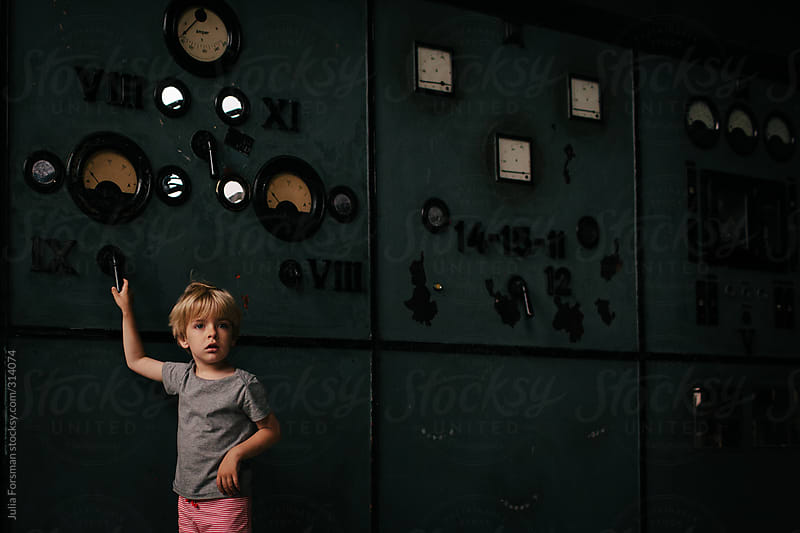 Boy pulls lever in disused power station. by Julia Forsman for Stocksy United