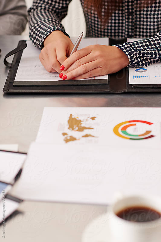 Business woman with red nails at desk with documents by Aila Images for Stocksy United