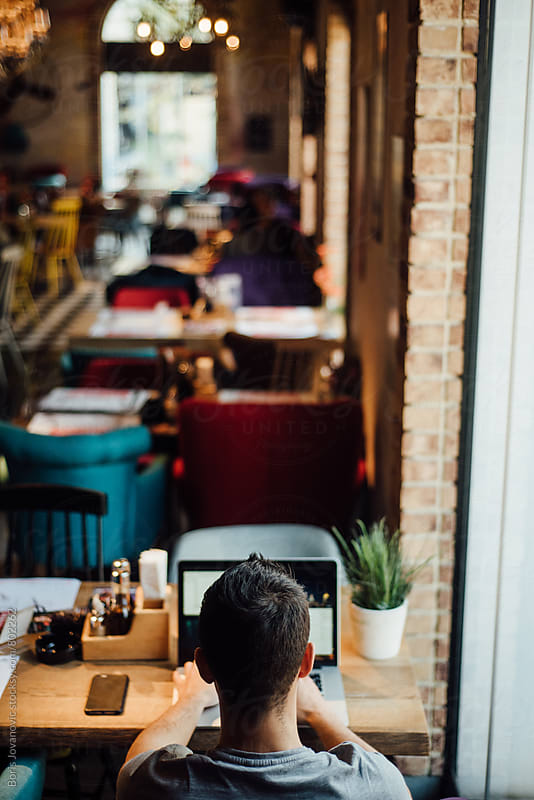 Man using a laptop in a cafe  by Boris Jovanovic for Stocksy United