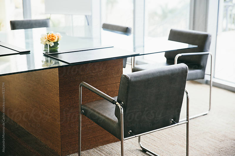 Glass desk and  office chairs in a meeting room by Alejandro Moreno de Carlos for Stocksy United