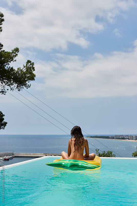 back view of topless brunette on inflatable in pool by Guille Faingold for Stocksy United