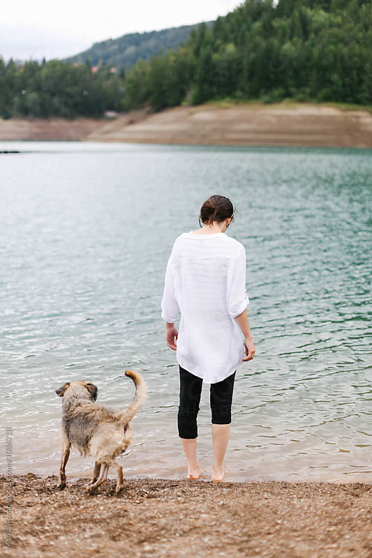 Woman and her dog at the beach, from behind by Marija Kovac for Stocksy United