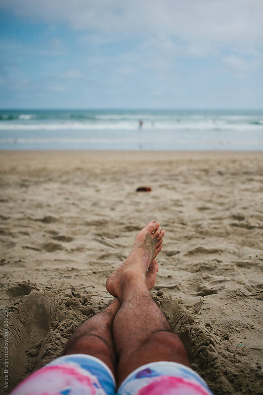 Legs of someone lying on the beach and the ocean by Ivo de Bruijn for Stocksy United