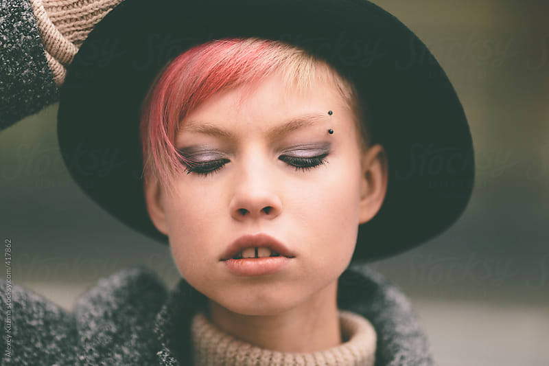 young woman with black hat and pink hair . by Alexey Kuzma for Stocksy United