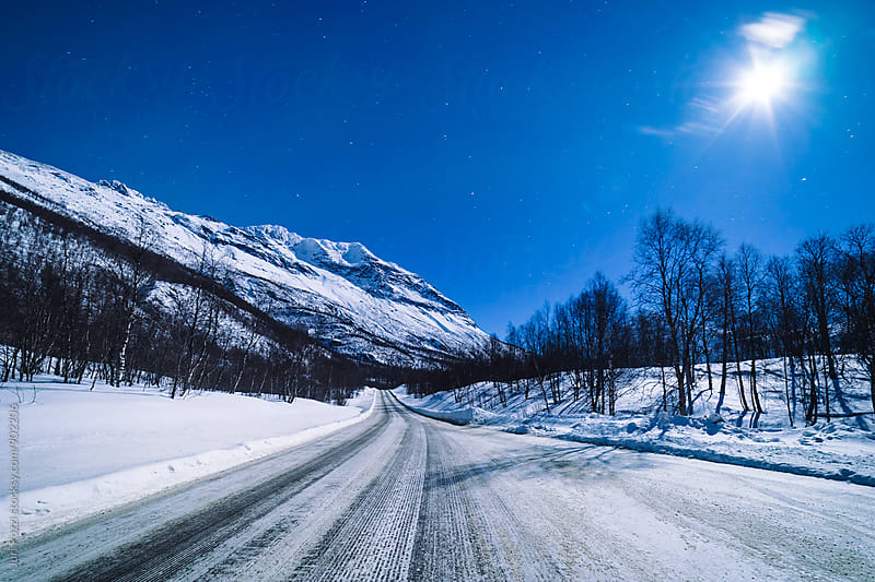 moonlight on a iced road in Norway by Juri Pozzi for Stocksy United