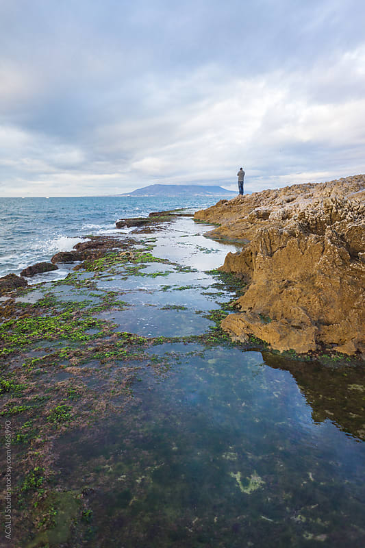 Young man on rock contemplating a seascape by ACALU Studio for Stocksy United