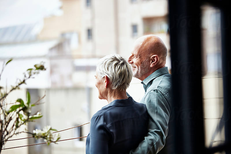 Smiling Senior Couple Admiring City On Balcony by ALTO IMAGES for Stocksy United