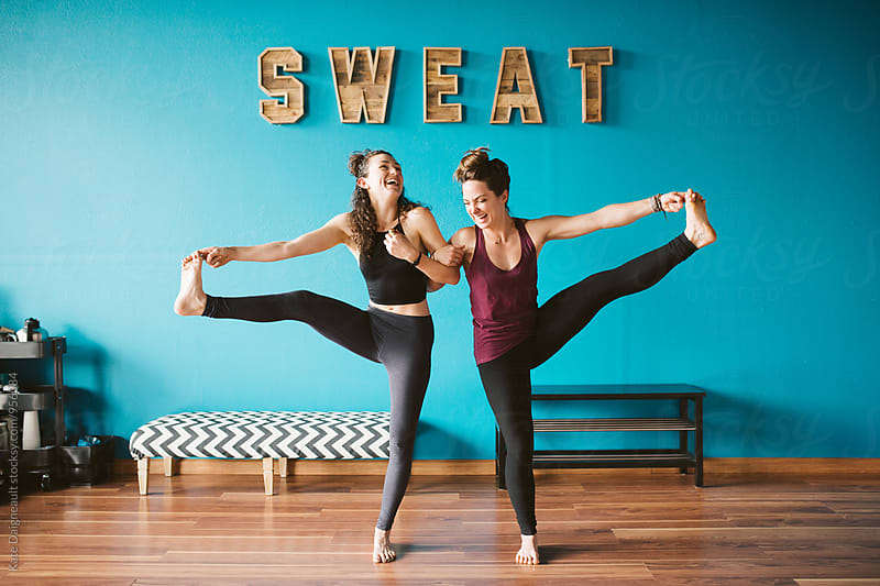 Two friends holding a yoga pose in a fitness studio by Kate Daigneault for Stocksy United