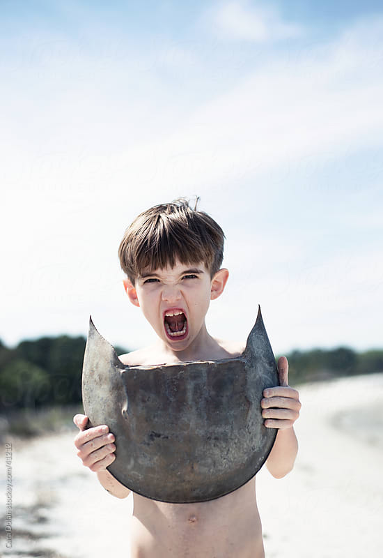 Boy makes warrior cry while holding large horseshoe crab shell by Cara Dolan for Stocksy United