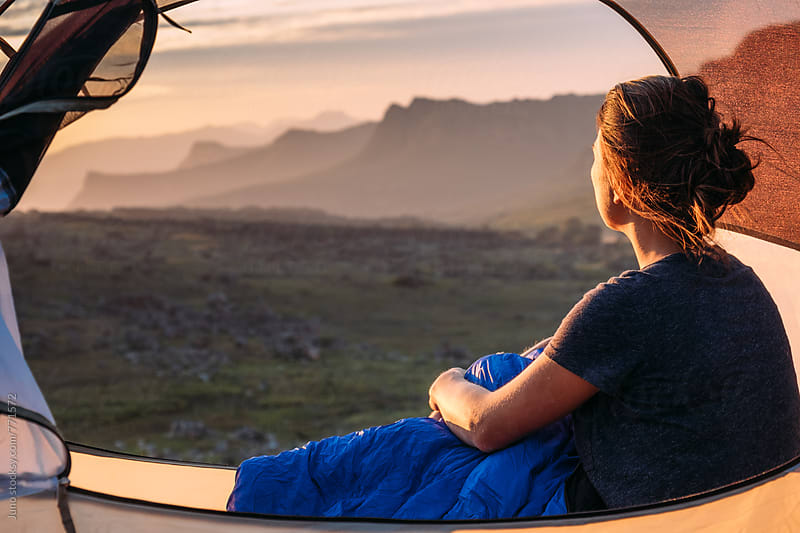 Woman sitting in her tent watching sunset over a mountain valley by Micky Wiswedel for Stocksy United