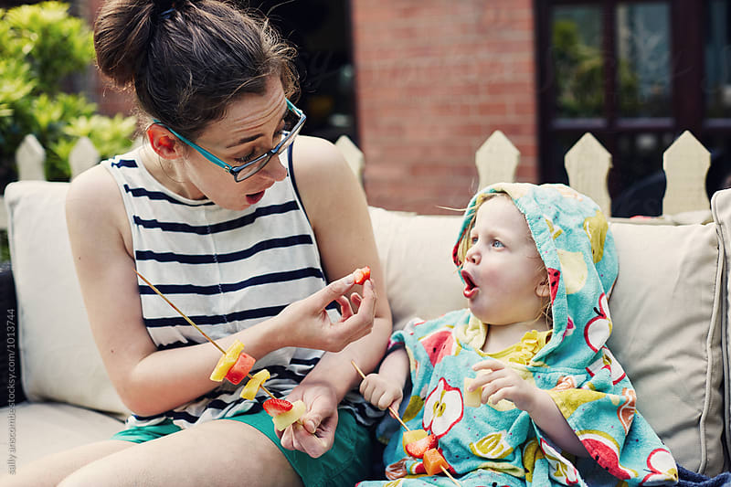 Young woman and toddler girl eating fruit kebabs by sally anscombe for Stocksy United