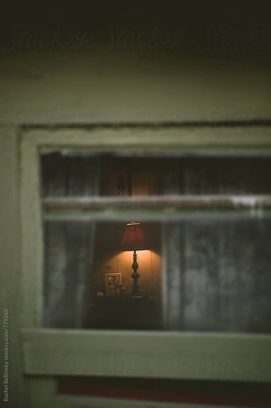 A lamp glows through the shabby window frame of an old house by Rachel Bellinsky for Stocksy United