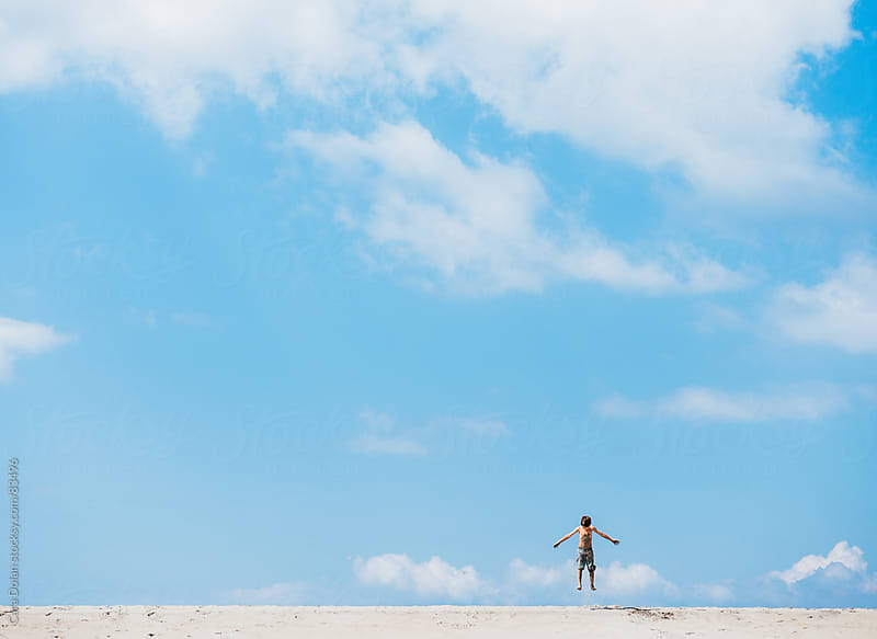 Boy jumps in the air on an empty beach under a blue sky by Cara Dolan for Stocksy United