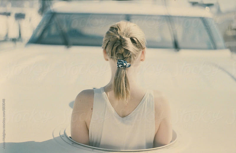 A film back photo of a blond woman on the yacht by Anna Malgina for Stocksy United
