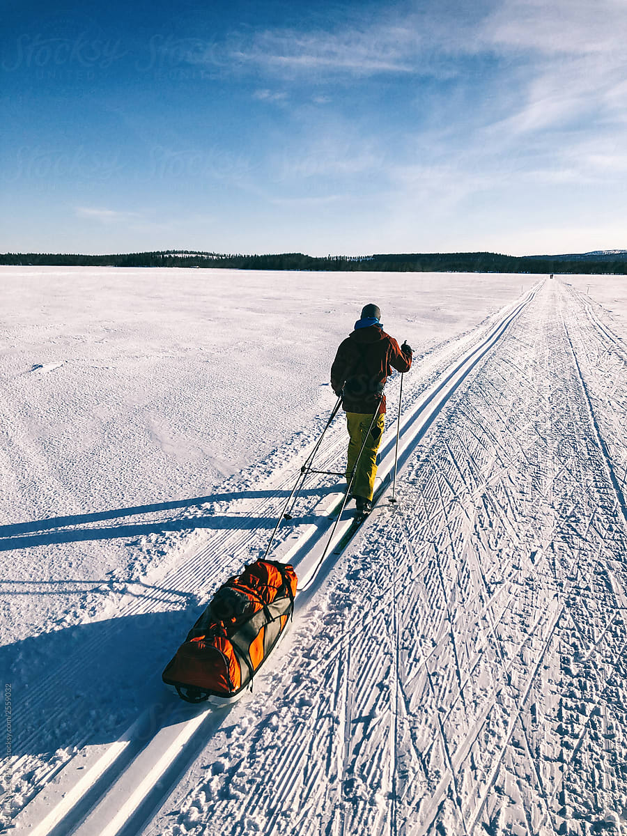 Stock Photo - Adventurer Ski Hiking With Sled On Frozen Lake
