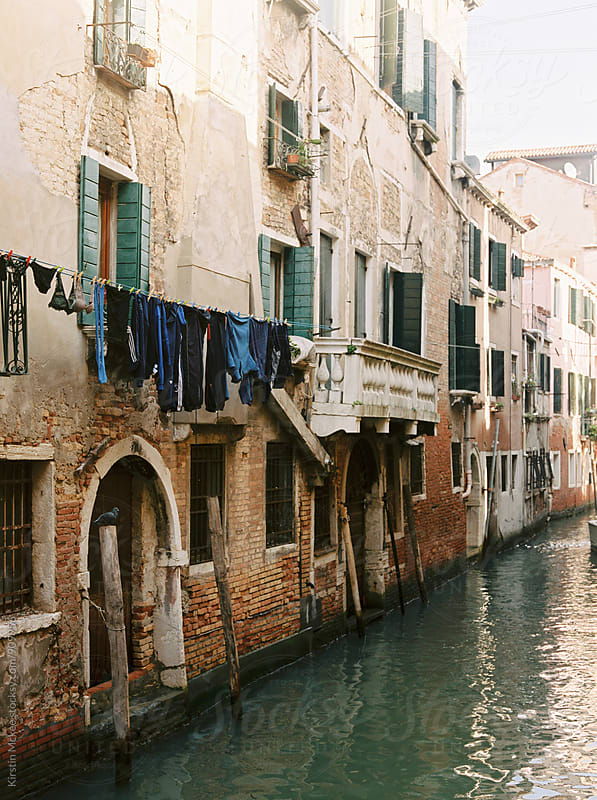 Washing line in front of building in Venice by Kirstin Mckee for Stocksy United