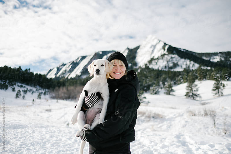 Woman smiling while holding her puppy in the snow with mountains in the distance by Kristine Weilert for Stocksy United
