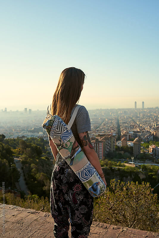 Back view of young woman with yoga bag looking at cityscape by Guille Faingold for Stocksy United