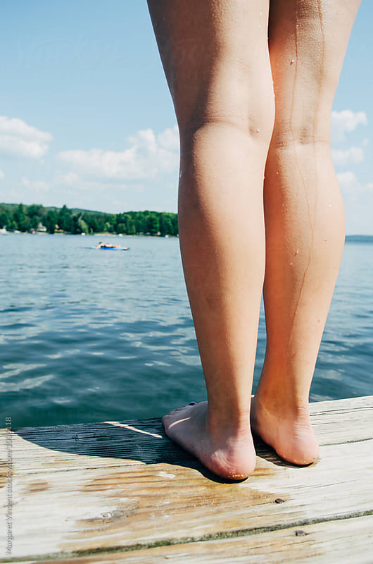 young woman's legs standing on a dock by Margaret Vincent for Stocksy United