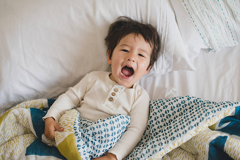 Cute kid laughing and lying down in bed by Lauren Naefe for Stocksy United