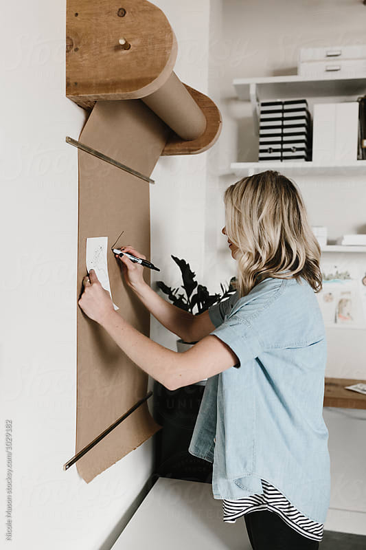young business owner drawing on roll of paper on wall by Nicole Mason for Stocksy United