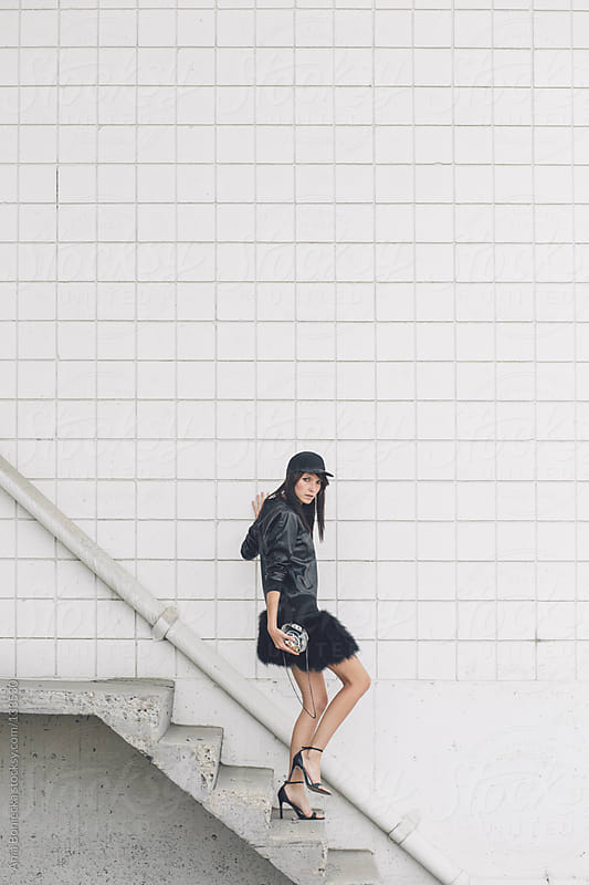 A woman walking down a flight of stairs dressed in all black by Ania Boniecka for Stocksy United