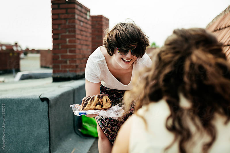 Young woman offering her friend some cake by VegterFoto for Stocksy United