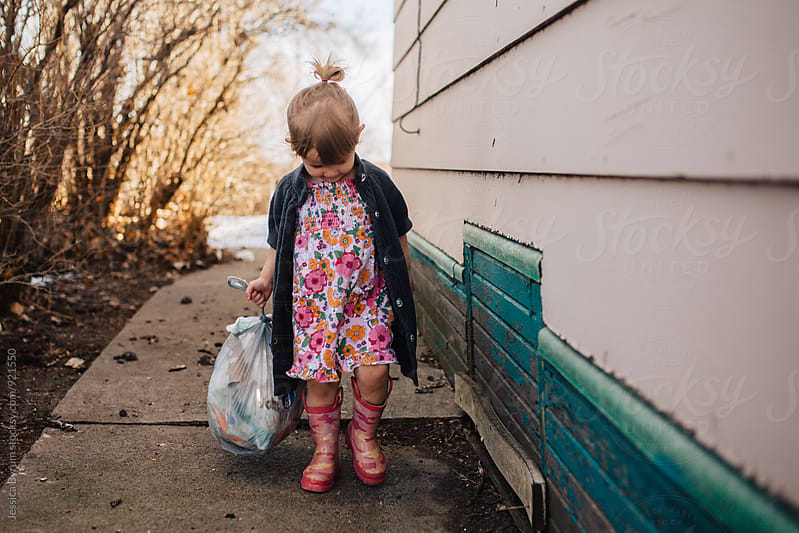 Toddler Girl Taking Out Some Trash by Jessica Byrum for Stocksy United