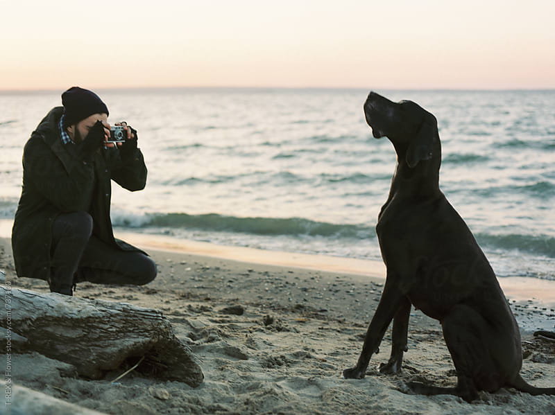 Man taking pictures of his dog at the beach by Danil Nevsky for Stocksy United