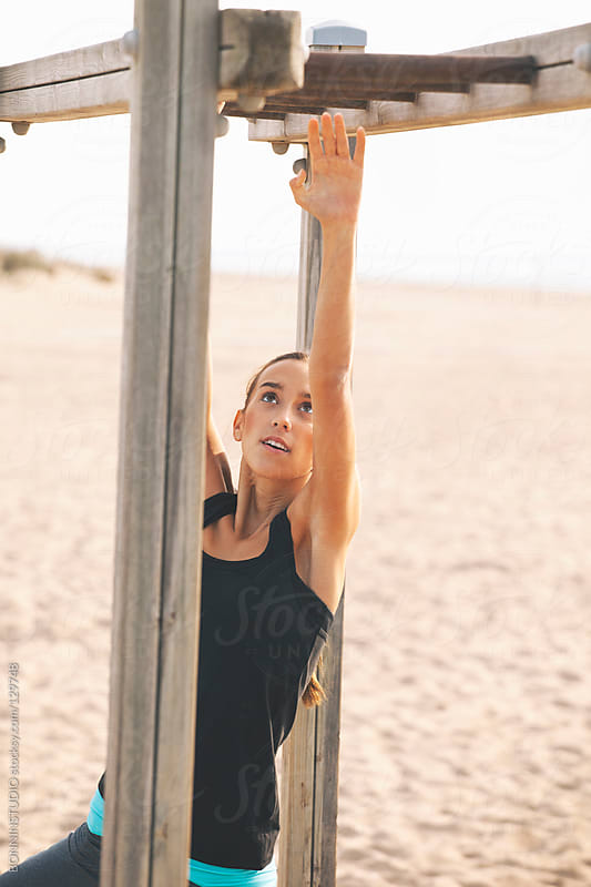 Fitness woman doing exercises on the beach. by BONNINSTUDIO for Stocksy United