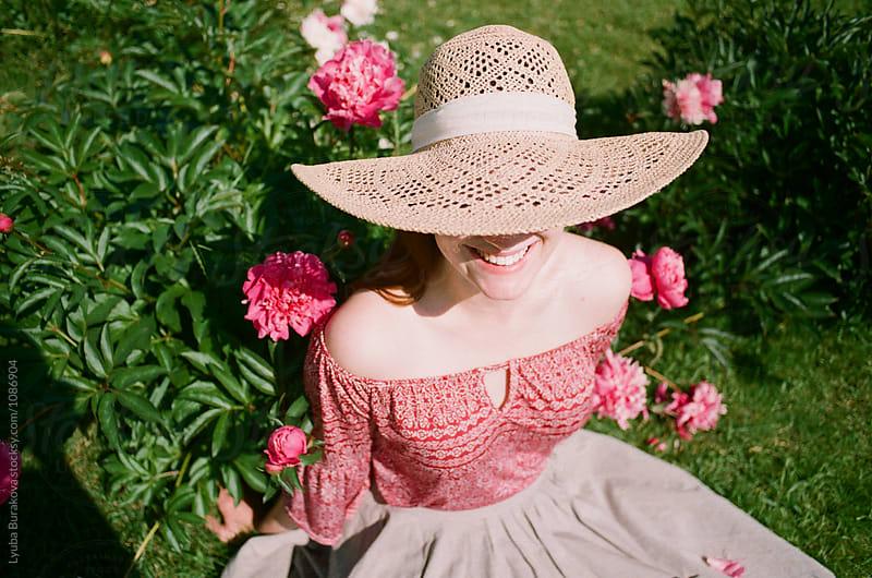 Happy woman wearing straw hat by Lyuba Burakova for Stocksy United
