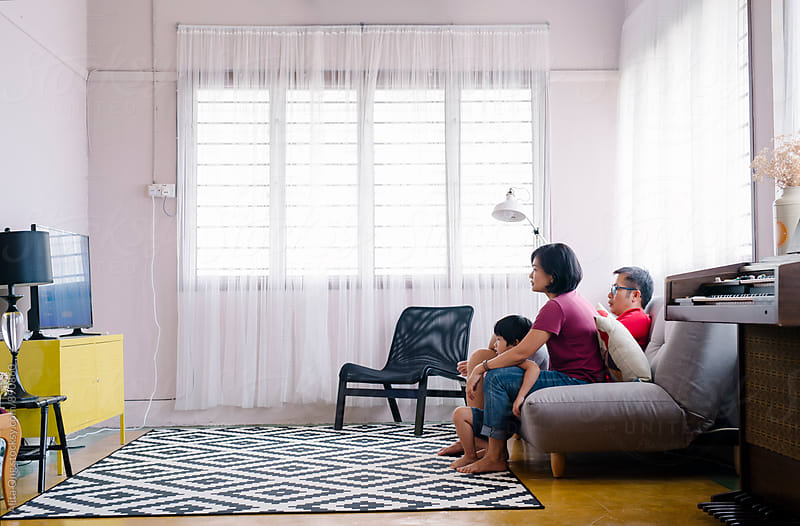 Family watching TV together by Alita Ong for Stocksy United