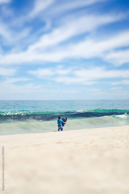 Boy about to boogie board by Angela Lumsden for Stocksy United