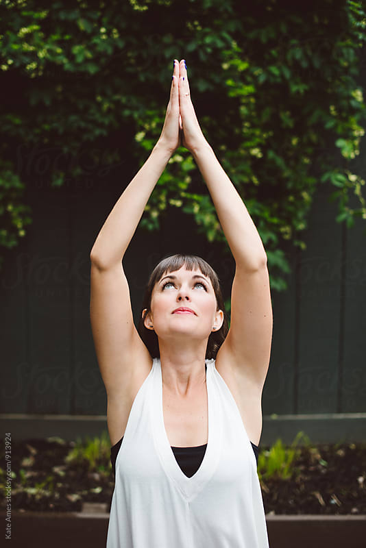 Young woman doing yoga in meditation garden by Kate Daigneault for Stocksy United