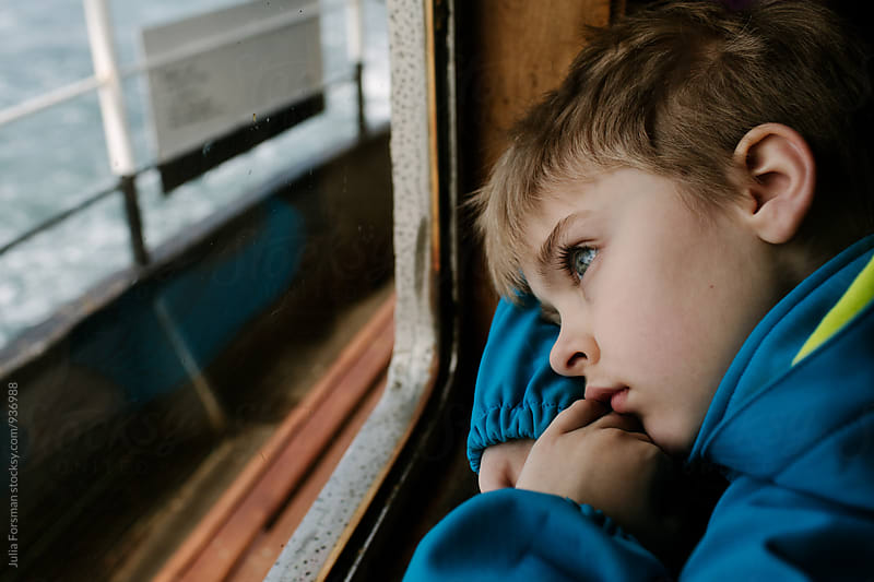 Boy stares out at the water while travelling by ferry. by Julia Forsman for Stocksy United