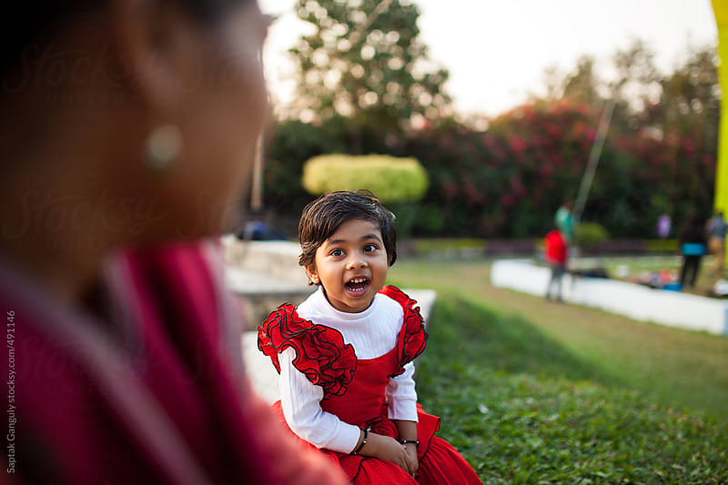 Cute toddler gossiping excitedly with her mother in a park  by Saptak Ganguly for Stocksy United