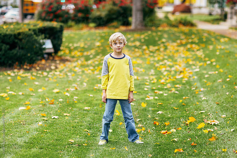 boy standing in a yard covered in autumn leaves by Kelly Knox for Stocksy United