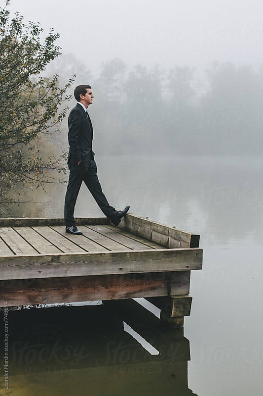 groom in wedding suit standing on a jetty looking at the lake by Leander Nardin for Stocksy United